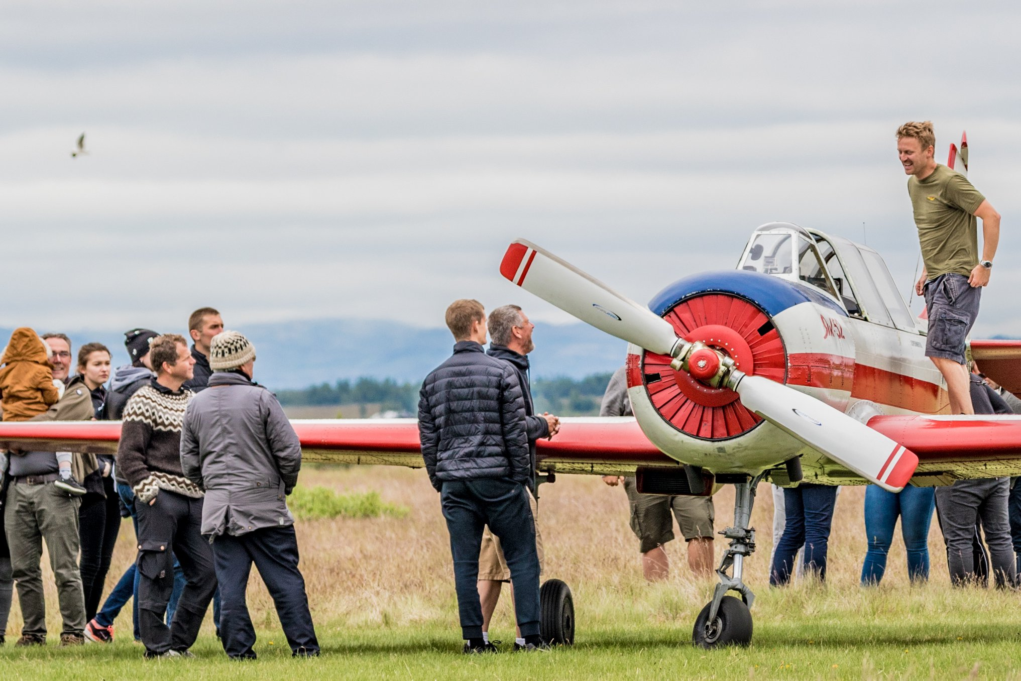 """Snorri Bjarnvin Jónsson is standing on the wing of Yak-52 TF-BCX before the show on the plane at """"Allt sem flýgur 2019"""" in Hella// Source: Andres Thorarinsson"""